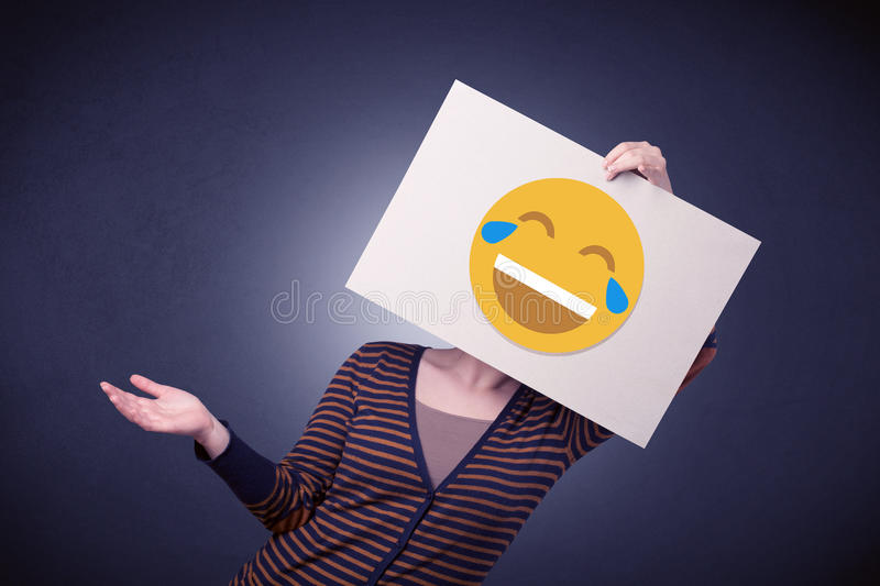 Woman holding paper with laughing emoticon. Young casual woman hiding behind a laughing emoticon on cardboard royalty free stock images