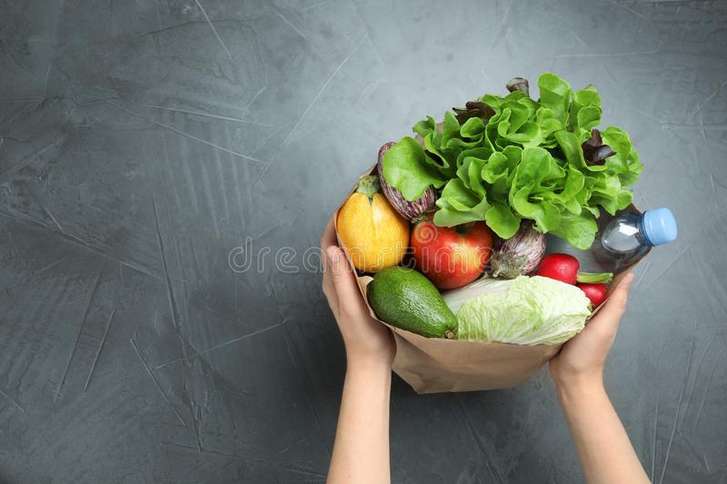 Woman holding paper package full of fresh vegetables and fruits on dark background, top view royalty free stock photos