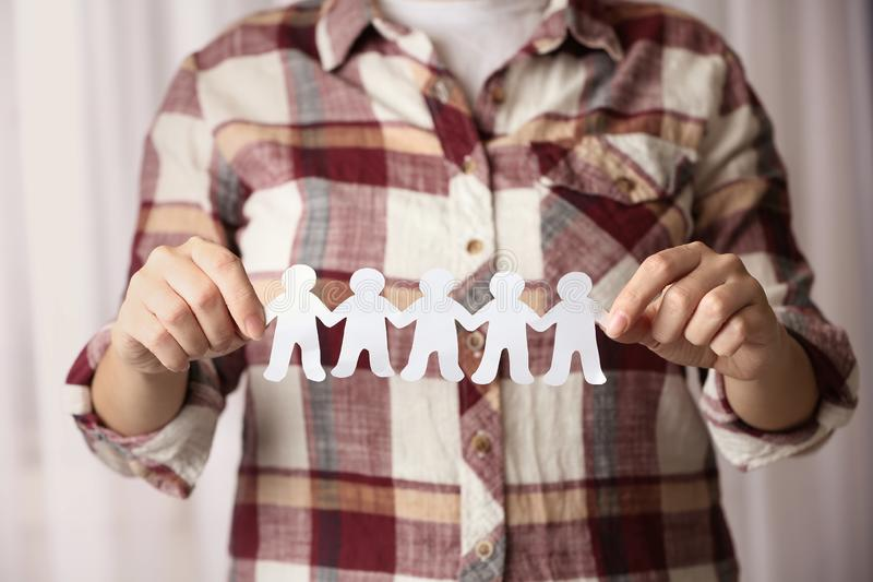 Woman holding paper people chain indoors. Unity concept. Woman holding paper people chain indoors, closeup. Unity concept stock images