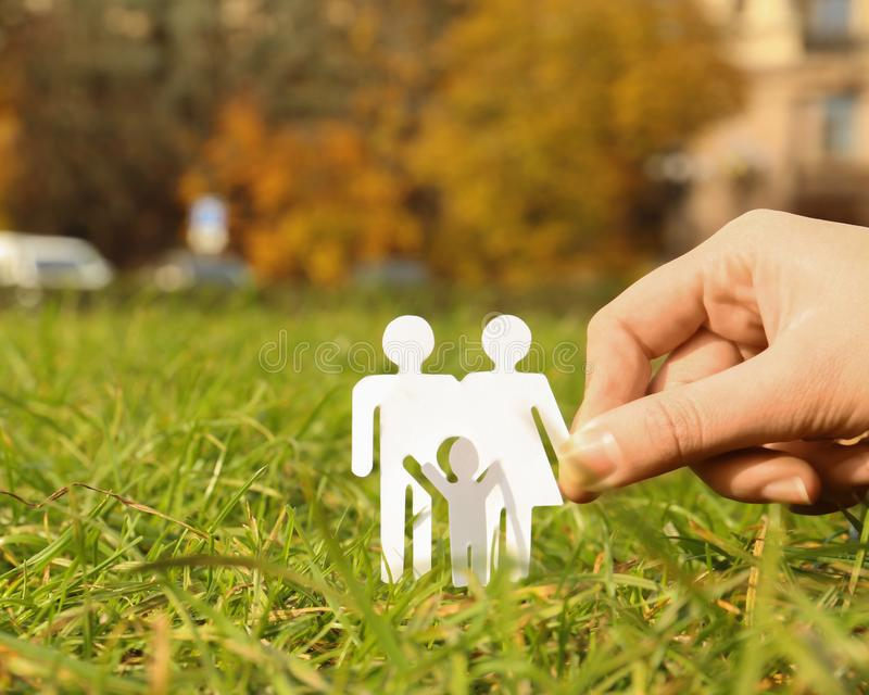 Woman holding paper silhouette of family in grass outdoors, space for text. Life insurance concept stock images