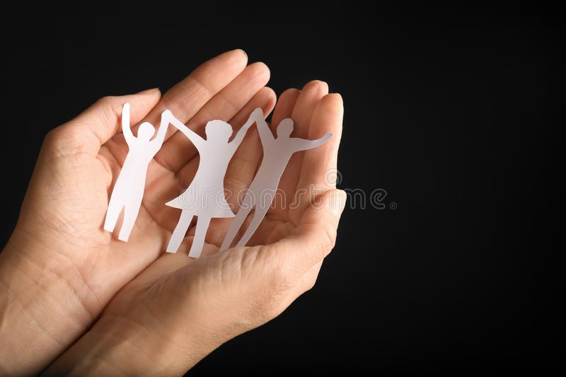 Woman holding paper  of family in hands on black background, closeup. Space for text. Woman holding paper silhouette of family in hands on black background stock photos