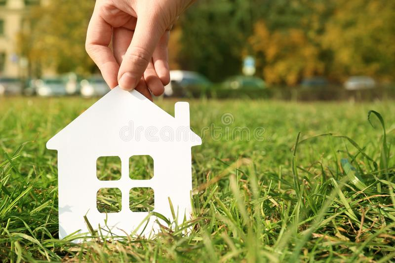 Woman holding paper silhouette of house in grass outdoors, space for text. Insurance concept stock photography