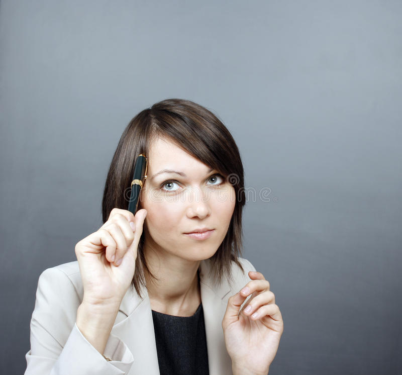 Woman holding a pen. Business woman holding a pen royalty free stock photos