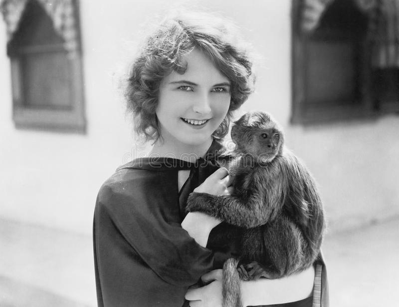 Woman holding a pet monkey in her arms. (All persons depicted are no longer living and no estate exists. Supplier grants that there will be no model release royalty free stock photography