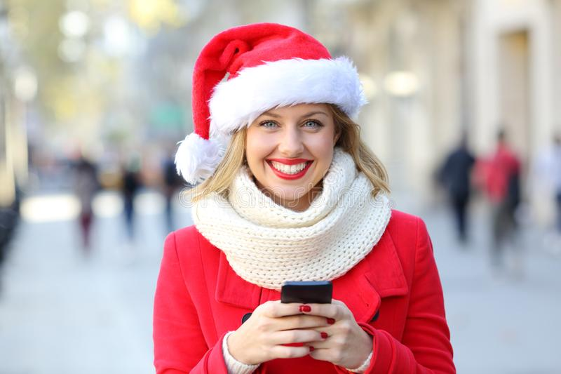 Woman holding a phone looking at you on christmas. Front view portrait of a happy woman holding a phone looking at you on christmas in the street stock image