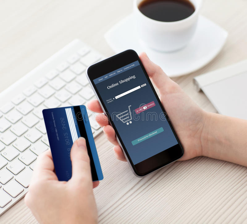 Woman holding phone with online shopping and a credit card royalty free stock photos