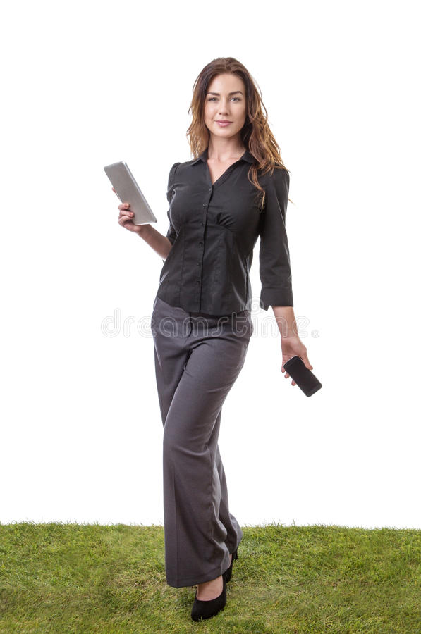 Woman holding phone and tablet. Pretty young model sanding on grass, holding her tablet computer in one hand and her mobile phone in the other stock photography
