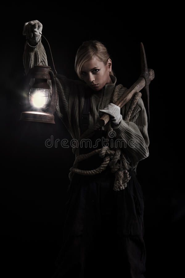 Woman holding pick and oil lamp. Woman holding heavy pick and oil lamp in hands stock image