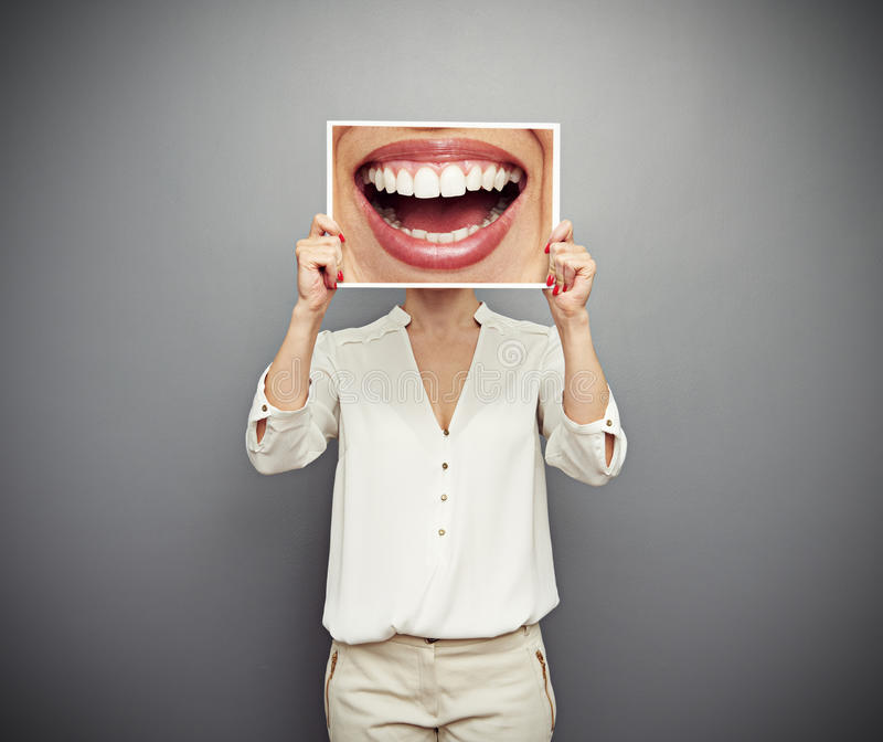 Woman holding picture with big smile stock images