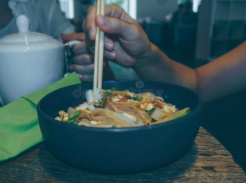 Woman holding piece of tofu in her chopsticks royalty free stock photo