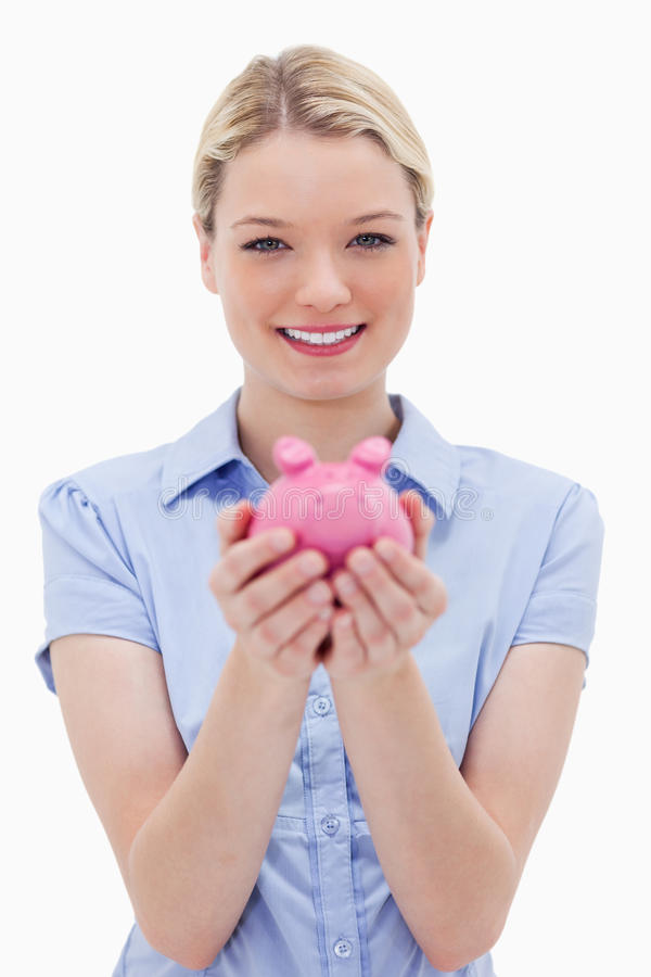 Woman holding piggy bank. Against a white background royalty free stock images