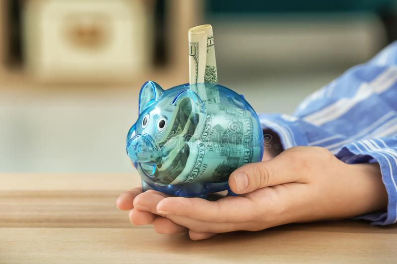 Woman holding piggy bank with money in hands. Savings concept royalty free stock image
