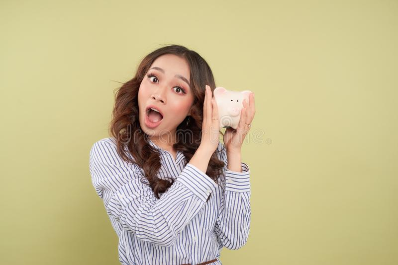 Woman holding piggy bank screaming and shouting excited and funny. Savings and banking with happy businesswoman holding pink piggy royalty free stock images
