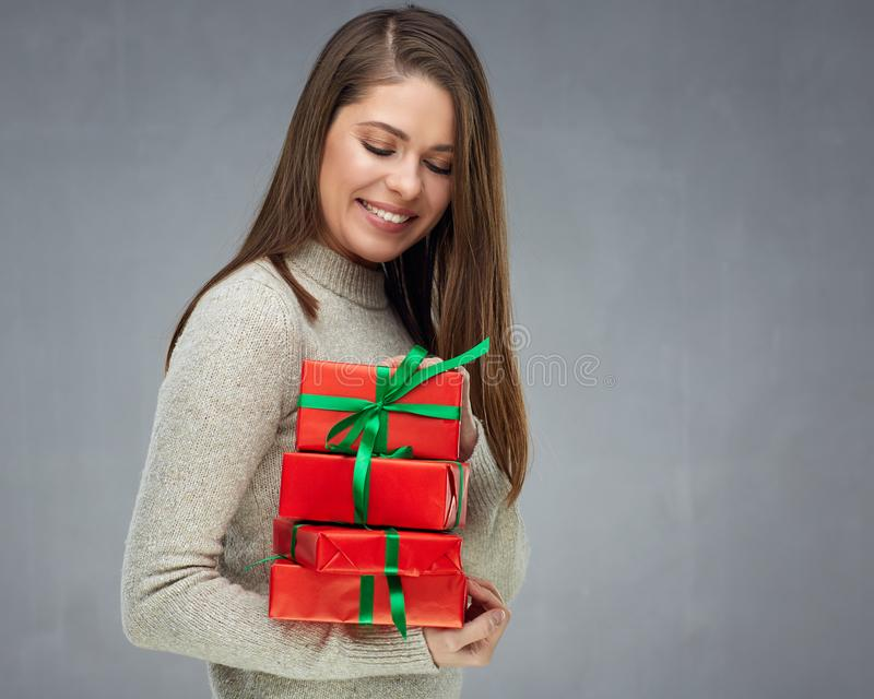 Woman holding pile of gifts and looking down at presents. royalty free stock photography