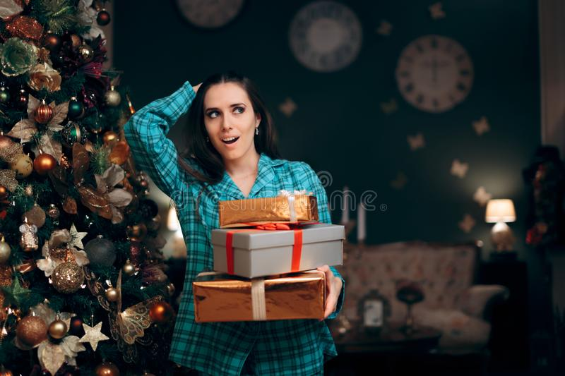 Woman Holding a Pile of  Presents near Christmas Tree royalty free stock photography