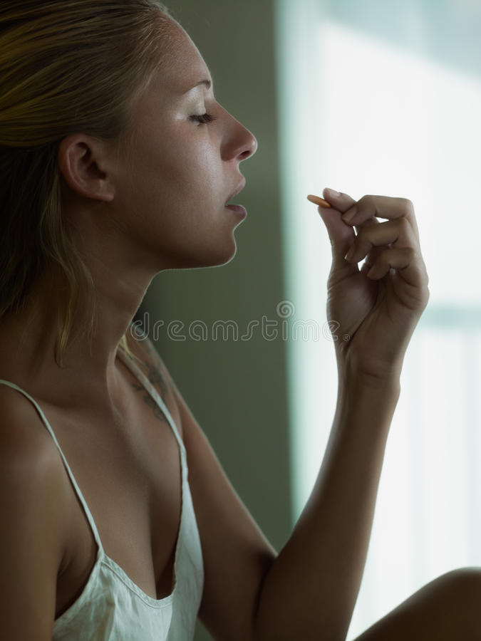 Woman holding pill royalty free stock photo