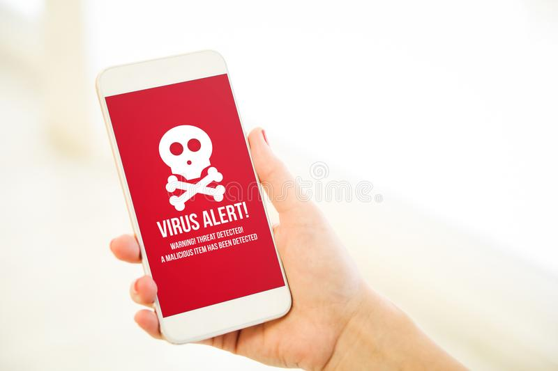 Woman holding a pink gold blank smartphone virus alert royalty free stock image