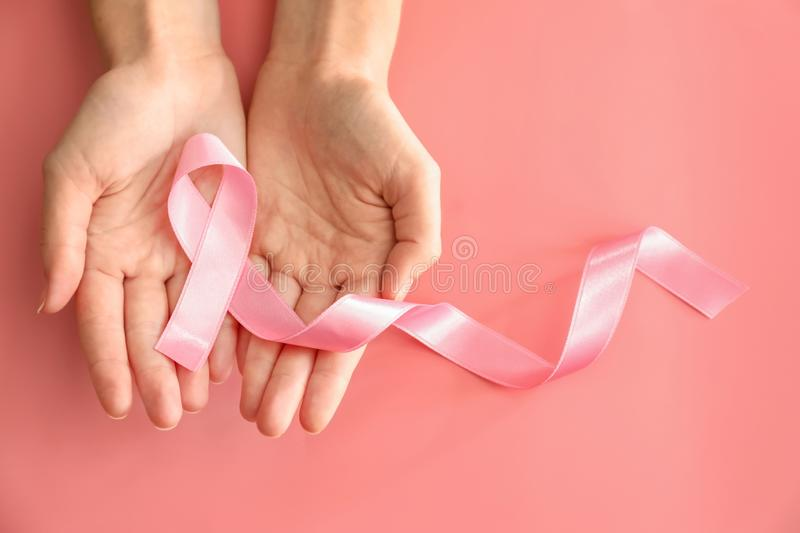 Woman holding pink ribbon on color background. Breast cancer awareness concept stock photography