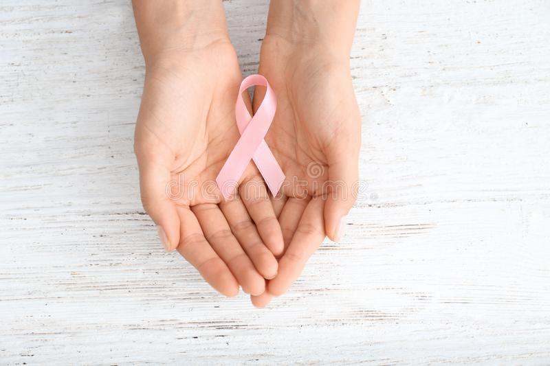 Woman holding pink ribbon on light wooden background. Breast cancer concept stock photography