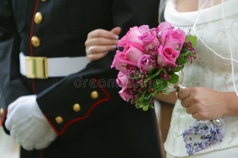 Woman Holding Pink Rose Wedding Bouquet Wearing White Wedding Dress stock photo