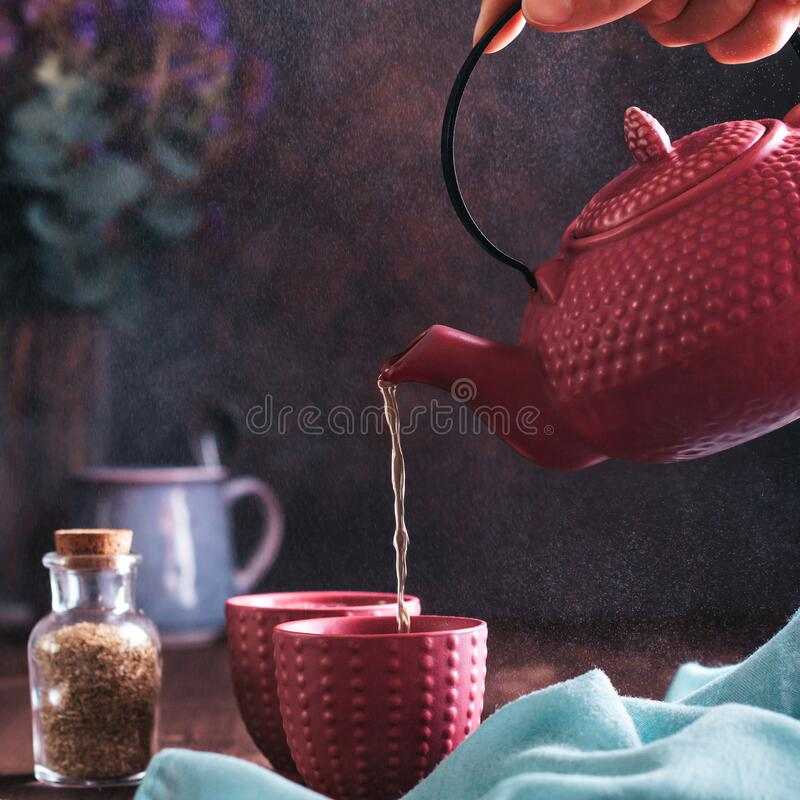 Free Woman Holding Pink Teapot And Pouring Herbal Chamomile Tea In Cups Against Dark Background, Square Format. Chinese Pink Royalty Free Stock Photos - 191306188