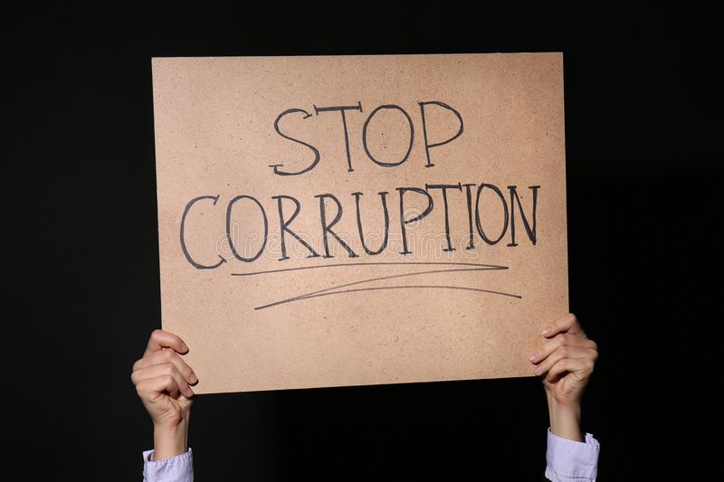 Woman holding placard with text STOP CORRUPTION on black background royalty free stock image