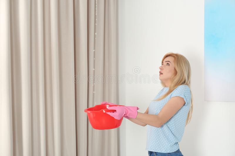 Woman holding plastic basin under water leakage from ceiling. At home stock photos