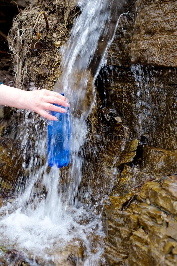 Woman holding a plastic bottle drawing clean water from cold spring. Drinking water source stock image