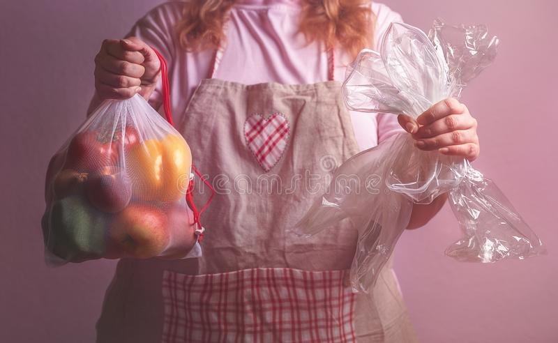Woman holding plastic wrappers versus eco bag for groceries royalty free stock image
