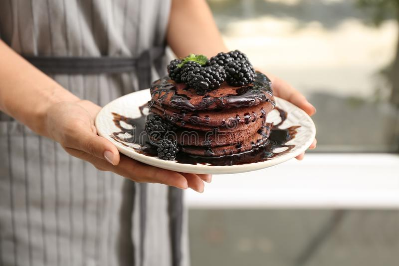 Woman holding plate with tasty chocolate pancakes, closeup stock photography
