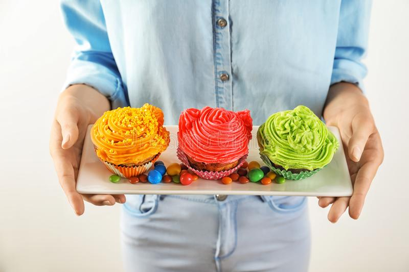 Woman holding plate with tasty colorful cupcakes and candies on light background, closeup royalty free stock photos