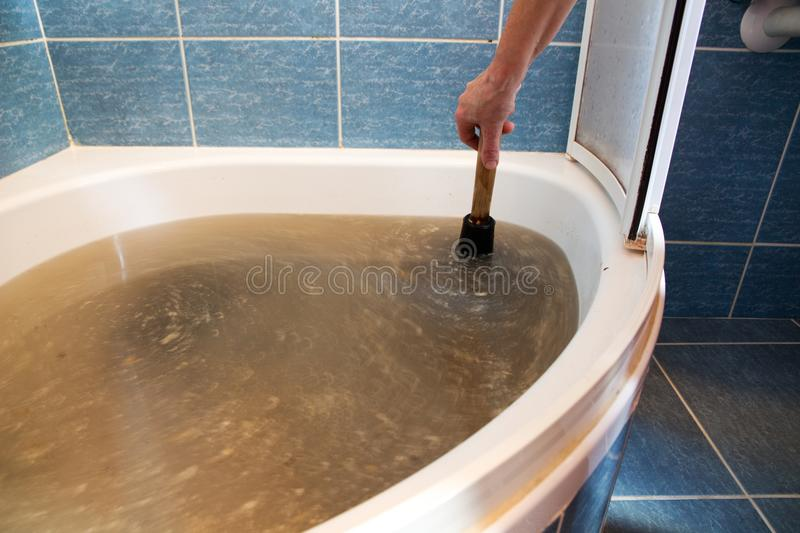 Woman holding a plunger to unblock drain. Woman's hand holding a plunger for use to unblock the drain from a bath with dirty water in it royalty free stock photography