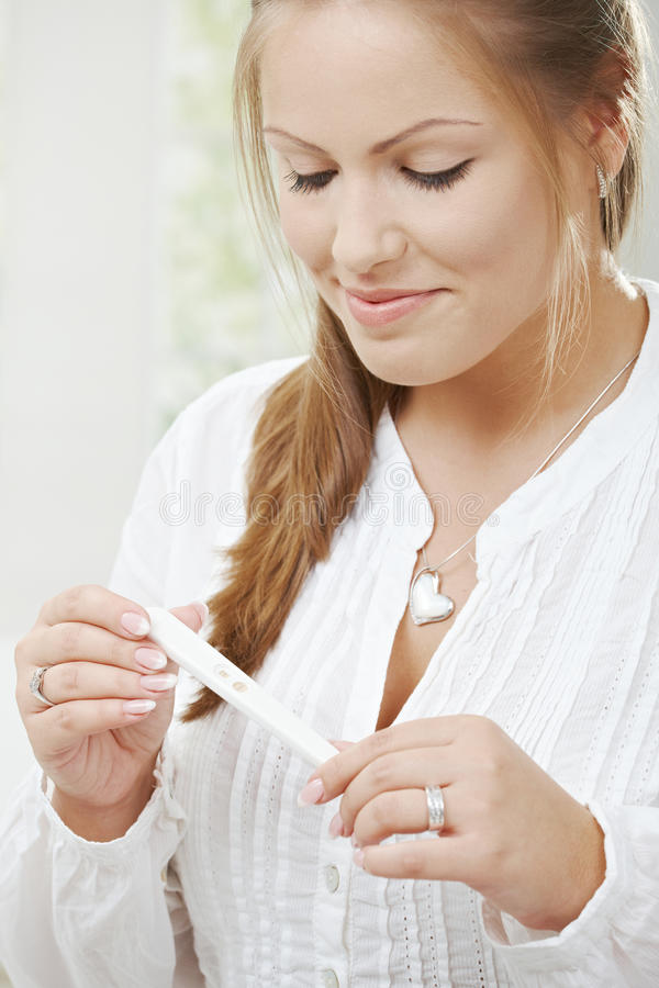 Woman holding pregnancy test stock photography