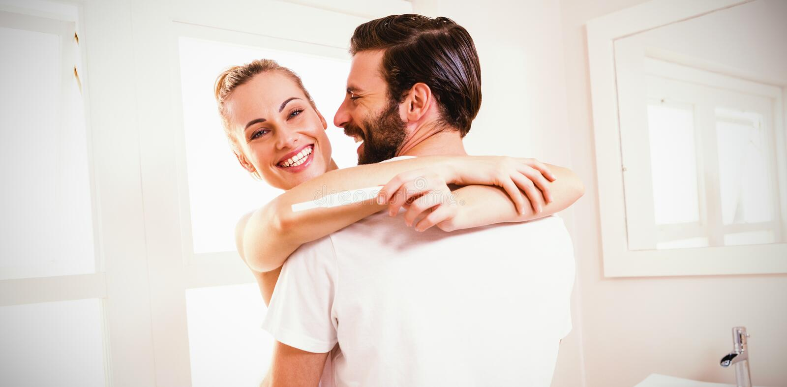Woman holding pregnancy test while embracing man stock photo
