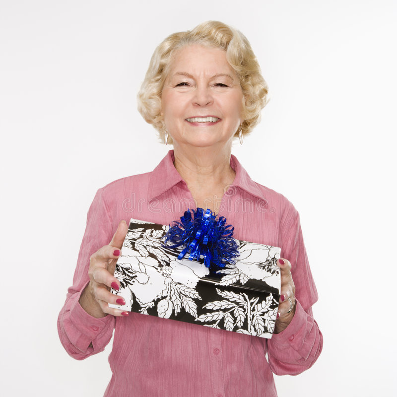 Woman holding present. Caucasian senior woman holding present smiling at viewer royalty free stock photos