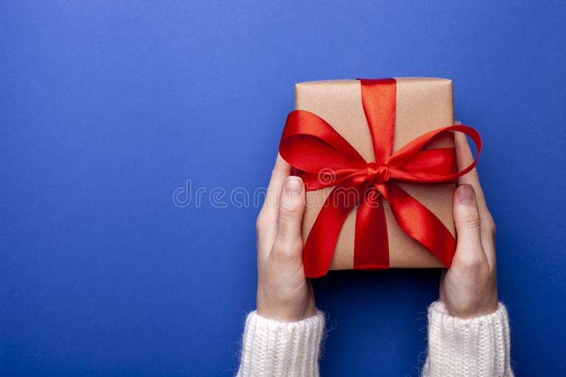 Woman holding present for Christmas on blue background. Female hands holding gift box wrapped in craft paper with red ribbon on co royalty free stock images