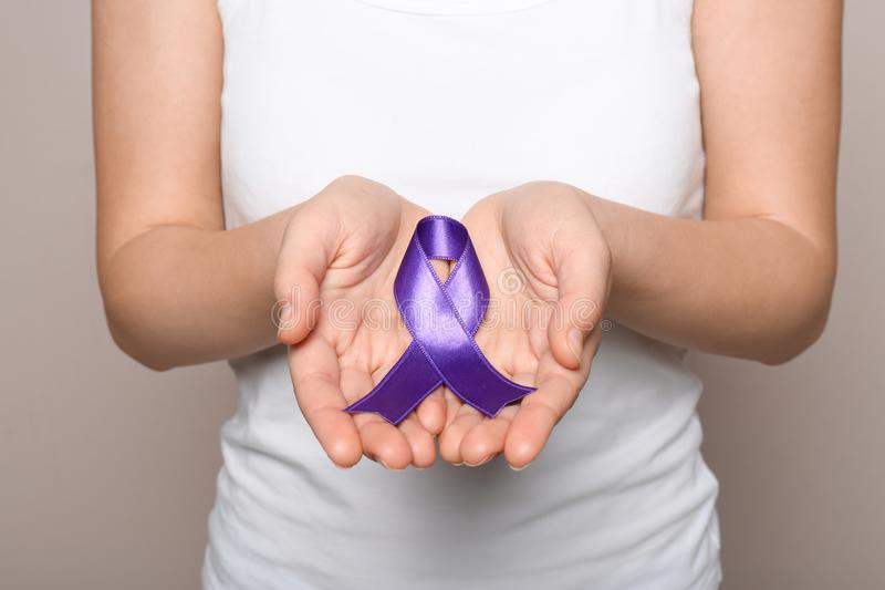 Woman holding purple ribbon on grey background. Domestic violence awareness. Woman holding purple ribbon on grey background, closeup. Domestic violence awareness royalty free stock images