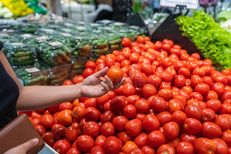 Woman holding purse and buying tomato at grocery store royalty free stock photos