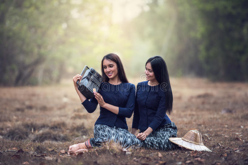 Woman Holding Radio in grass field royalty free stock images