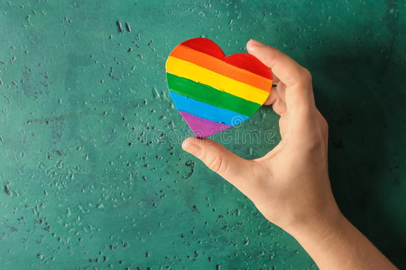 Woman holding rainbow heart shaped painting of LGBT on color background royalty free stock photo