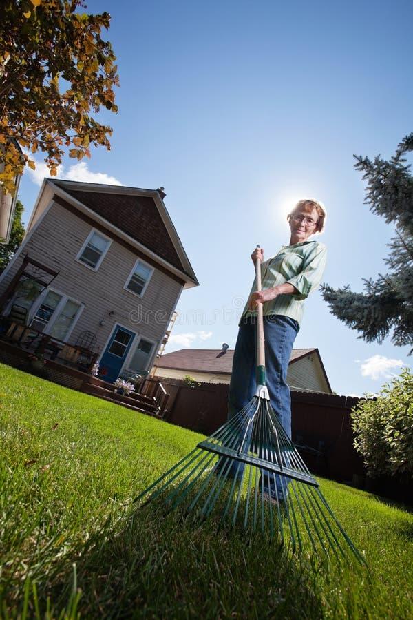 Woman holding rake stock photos