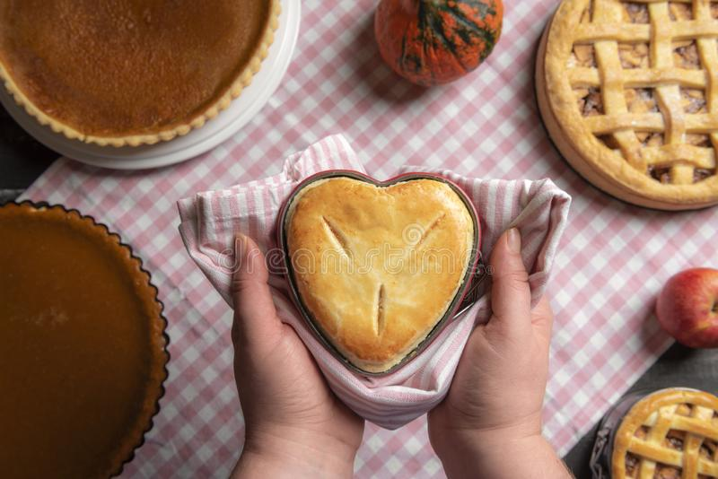 Woman holding a raspberry pie, in a heart-shaped tray, above a kitchen table full of traditional fall pies, apple pies, and royalty free stock image