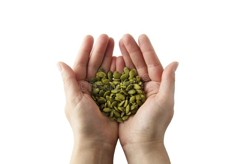 Woman holding raw unshelled pumpkin seeds, closeup view, isolated. Healthy, vegetarian super food or snack. Template for design royalty free stock photo