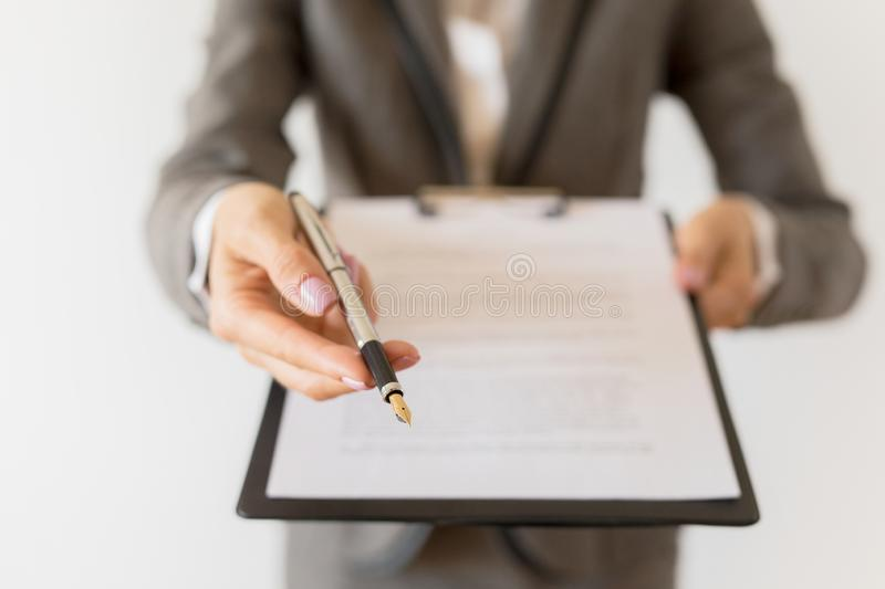 Woman holding ready to sign contract and pen royalty free stock images