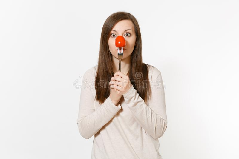 Woman holding red fresh tomato on fork in front nose like clown isolated on white background. Proper nutrition stock photo