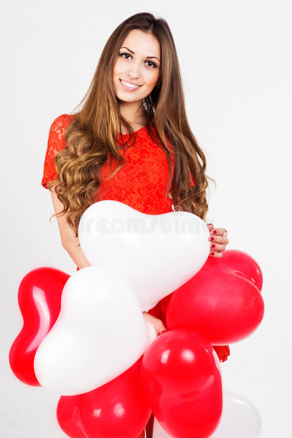 Woman holding red heart balloons. Valentines day smiling woman is wearing red fashion dress holding red and white heart balloons royalty free stock image