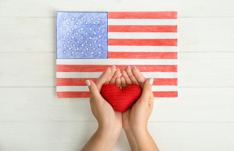 Woman holding red heart near drawing of American national flag on white wooden table royalty free stock image