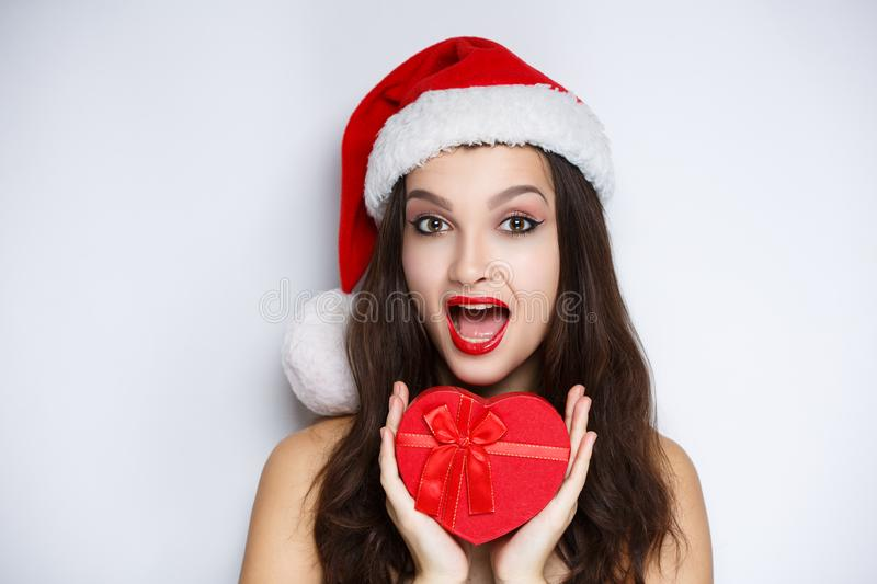 Woman holding red heart, santa with present. Beauty face close-up photo portrait. Beautiful girl wearing Christmas red hat cap. Pretty woman stylish make up royalty free stock photo