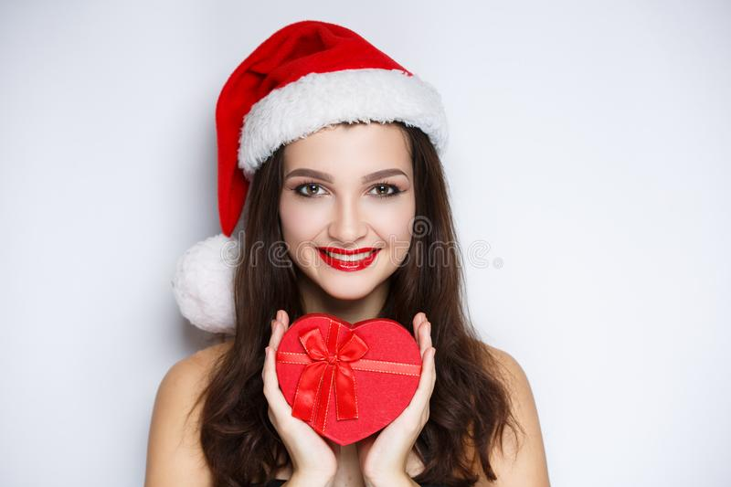Woman holding red heart, santa with present. Beauty face close-up photo portrait. Beautiful girl wearing Christmas red hat cap. Pretty woman stylish make up stock photo