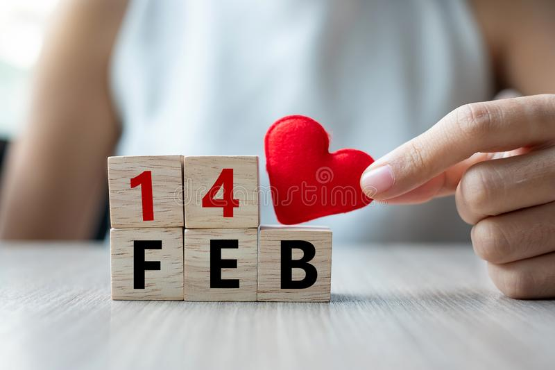 Woman holding red heart shape decoration iwith wooden cube on table background. Love, Wedding, Romantic and Happy Valentines day stock images